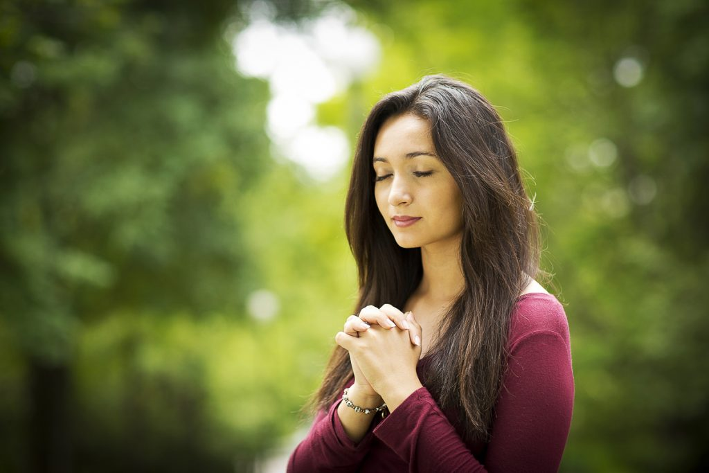 Woman hands praying with a blible in his legs Outdoors